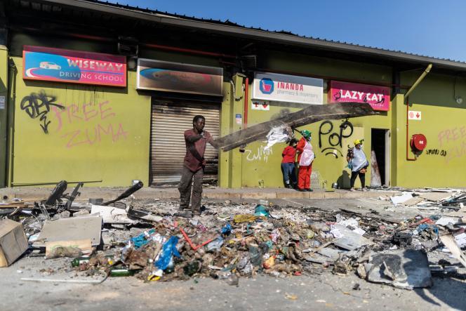 Des membres de la communauté Inanda nettoient le centre commercial Dube Village Mall, qui a été pillé, à Durban (Afrique du Sud), le 17 juillet 2021.