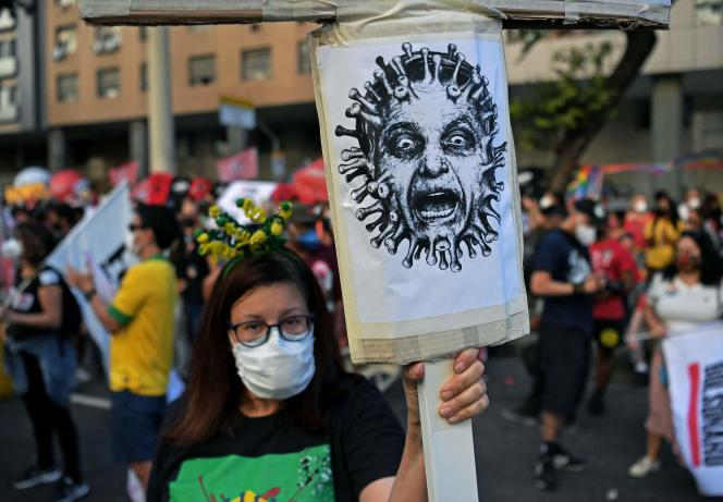 July 24, 2021, in Rio de Janeiro, a protester holding a portrait of a virally dressed Bolsanaro.