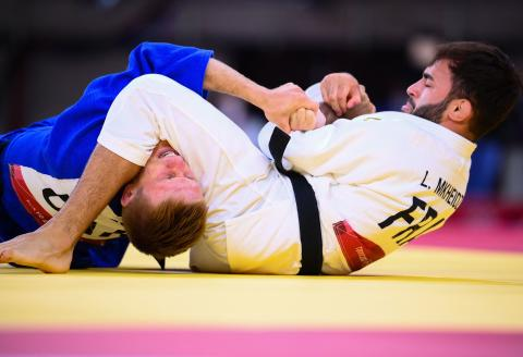 TOPSHOT - France's Luka Mkheidze (white) competes with Ukraine's Artem Lesiuk during their judo men's -60kg quarterfinal bout during the Tokyo 2020 Olympic Games at the Nippon Budokan in Tokyo on July 24, 2021. (Photo by Franck FIFE / AFP)