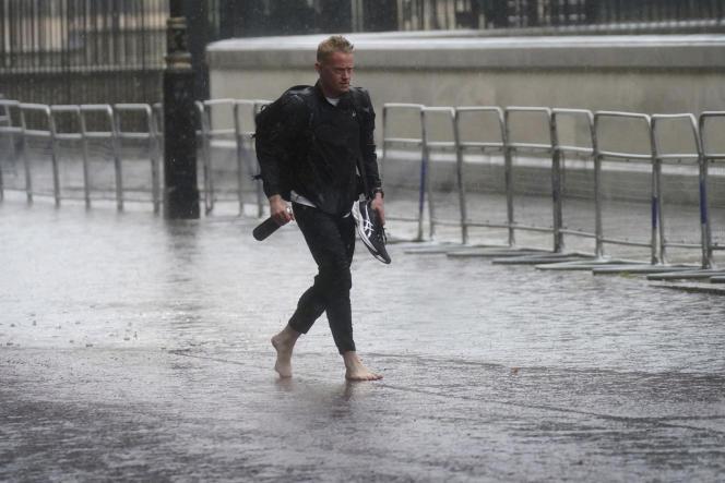 Un uomo cammina a piedi nudi in una strada allagata nel centro di Londra il 25 luglio.