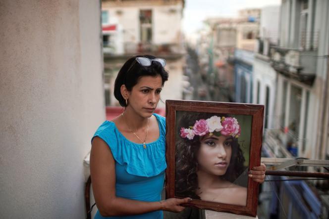 Une mère pose avec le portrait de sa fille, détenue par la police suite à une manifestation, à La Havane, le 20 juillet 2021.
