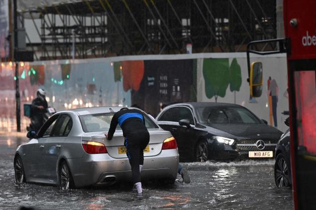 Ein Autofahrer muss am 25. Juli 2021 sein Auto auf einer überfluteten Londoner Straße in den Nine Elms schieben.
