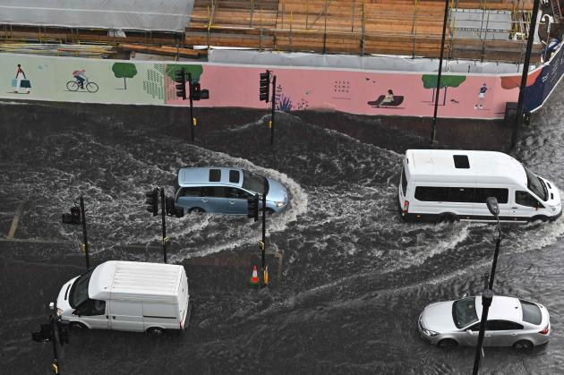 Cars drive through a flooded London street in the Nine Elms district on 25 July 2021.