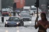 Des voitures traversent une rue inondée de Londres, dans le quartier de Nine Elms, le 25 juillet 2021.