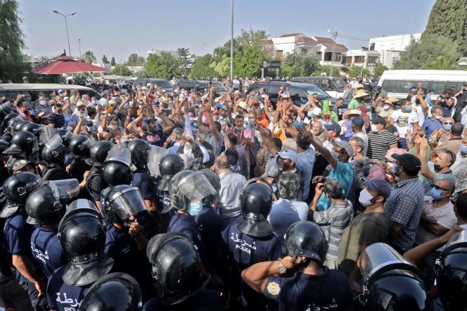 Des policiers tunisiens retiennent des manifestants devant le bâtiment du Parlement, à Tunis, le 26 juillet 2021.