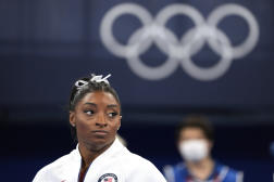 L'Américaine Simone Biles observe ses coéquipières lors du concours général par équipes, mardi 27 juillet, au gymnase d'Ariake à Tokyo.