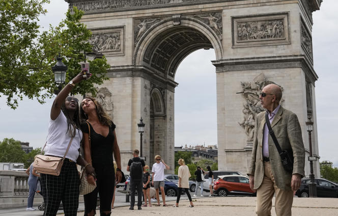 Two young women take a selfie at the foot of the Arc de Triomphe in Paris on June 17, 2021.
