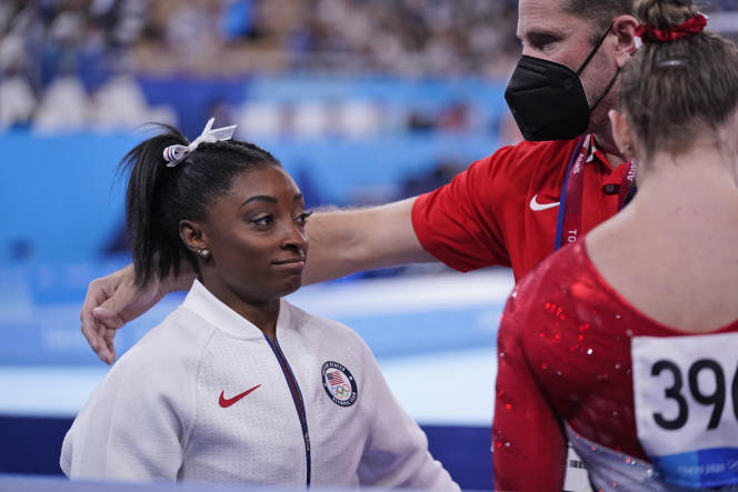 Simone Biles, ici consolée par son entraîneur Laurent Landi, s'est retirée du concours de gymnastique par équipes, mardi.