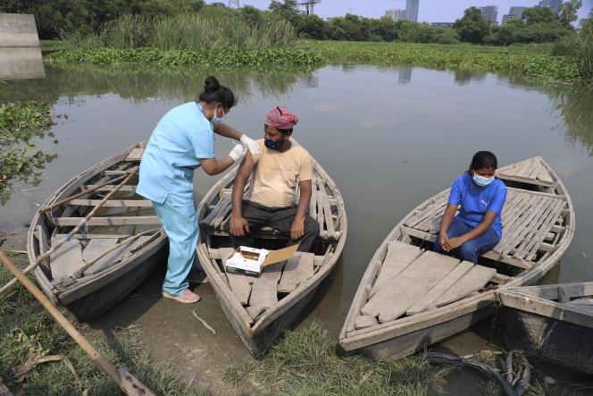 Un travailleur de la santé administre le vaccin contre le Covid-19 à un batelier sur la rivière Yamuna, en Inde, le 16 juillet 2021.
