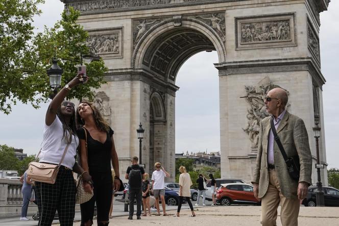 Deux jeunes femmes prennent un selfie au pied de l'Arc de Triomphe, à Paris, le 17 juin 2021.