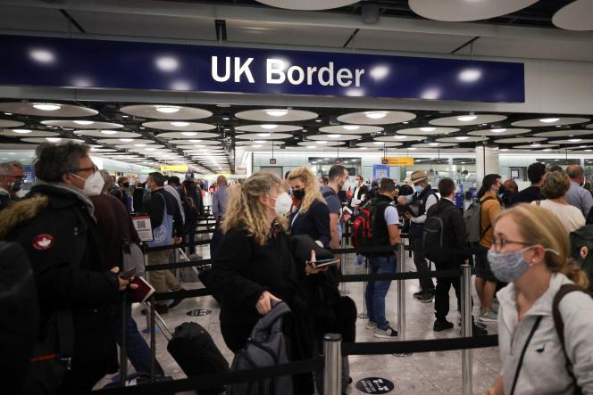 Des voyageurs patientent au niveau de l'entrée sur le sol britannique, à l'aéroport de Heathrow, à Londres, en juin 2021.
