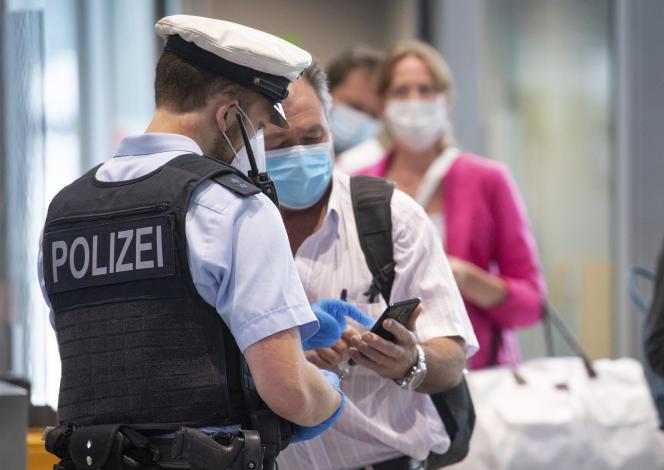 Des agents de police contrôlent les passagers arrivant à bord d'un vol en provenance du Portugal, à l'aéroport de Francfort, le 29 juin 2021.