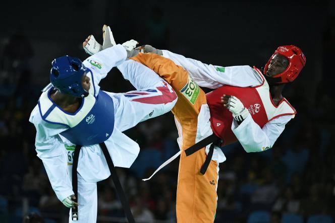 L'Ivoirien Cheick Cissé (à droite) affronte le Britannique Lutalo Muhammad pour la médaille d'or de taekwondo dans la catégorie des moins de 80 kg, lors des Jeux olympiques de Rio, le 19 août 2016.