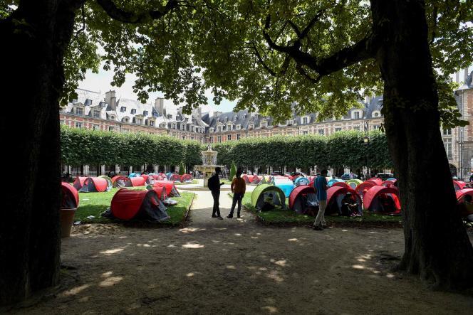 Des manifestants se tiennent autour de tentes installées par l'association Utopia pour demander des logements pour les migrants et les sans-abri, sur la place des Vosges à Paris, le 29 juillet 2021.