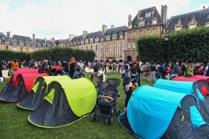 Des familles attendent place des Vosges pour demander des logements, à Paris, le 29 juillet 2021.