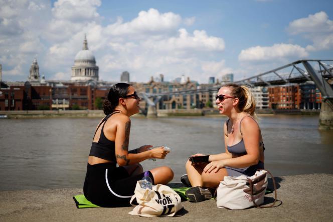 Deux amies sont assises près de la Tamise, à Londres, alors que la température atteignait 31 °C, le 26 juin 2020.