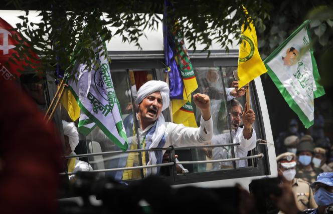 Des agriculteurs crient des slogans alors qu'ils arrivent dans un bus pour assister à un sit-in de protestation contre les lois agricoles, près du parlement, à New Delhi, en Inde, le 22 juillet 2021.