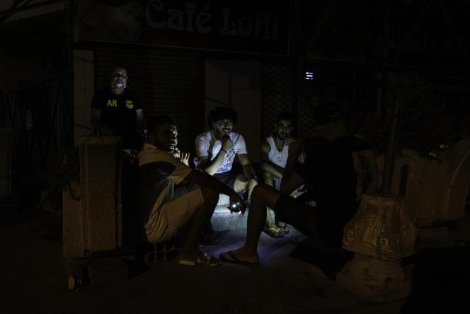 De jeunes Tunisiens, Sahbi, Oussama, Hammadi et Houssem, devant un café fermé après le début du couvre-feu, à 19 heures à Sfax, le 29 juillet 2021.