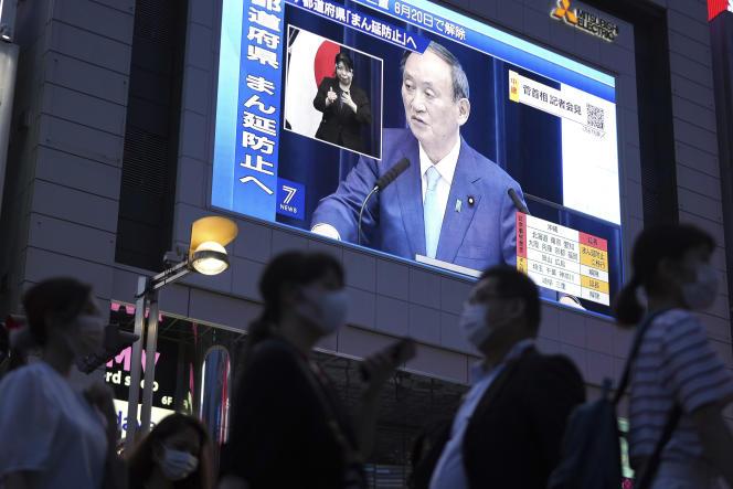 Des gens passent devant un grand écran, tandis que le premier ministre japonais, Yoshihide Suga, s'exprime sur la situation sanitaire du pays, à Tokyo,le 17 juin 2021.
