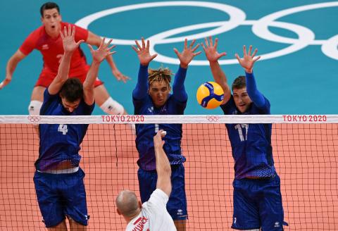 Poland's Bartosz Kurekin hits the ball in front of (L-R) France's Jean Patry, Barthelemy Chinenyeze and Trevor Clevenot in the men's quarter-final volleyball match between Poland and France during the Tokyo 2020 Olympic Games at Ariake Arena in Tokyo on August 3, 2021. (Photo by YURI CORTEZ / AFP)