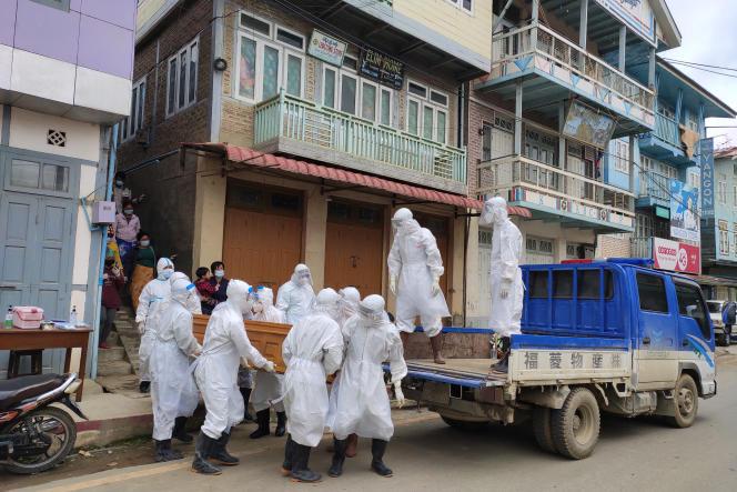 Du personel médical porte le cercueil d'une victime du Covid-19 le 29 juin 2021 à Tedim, en Birmanie.