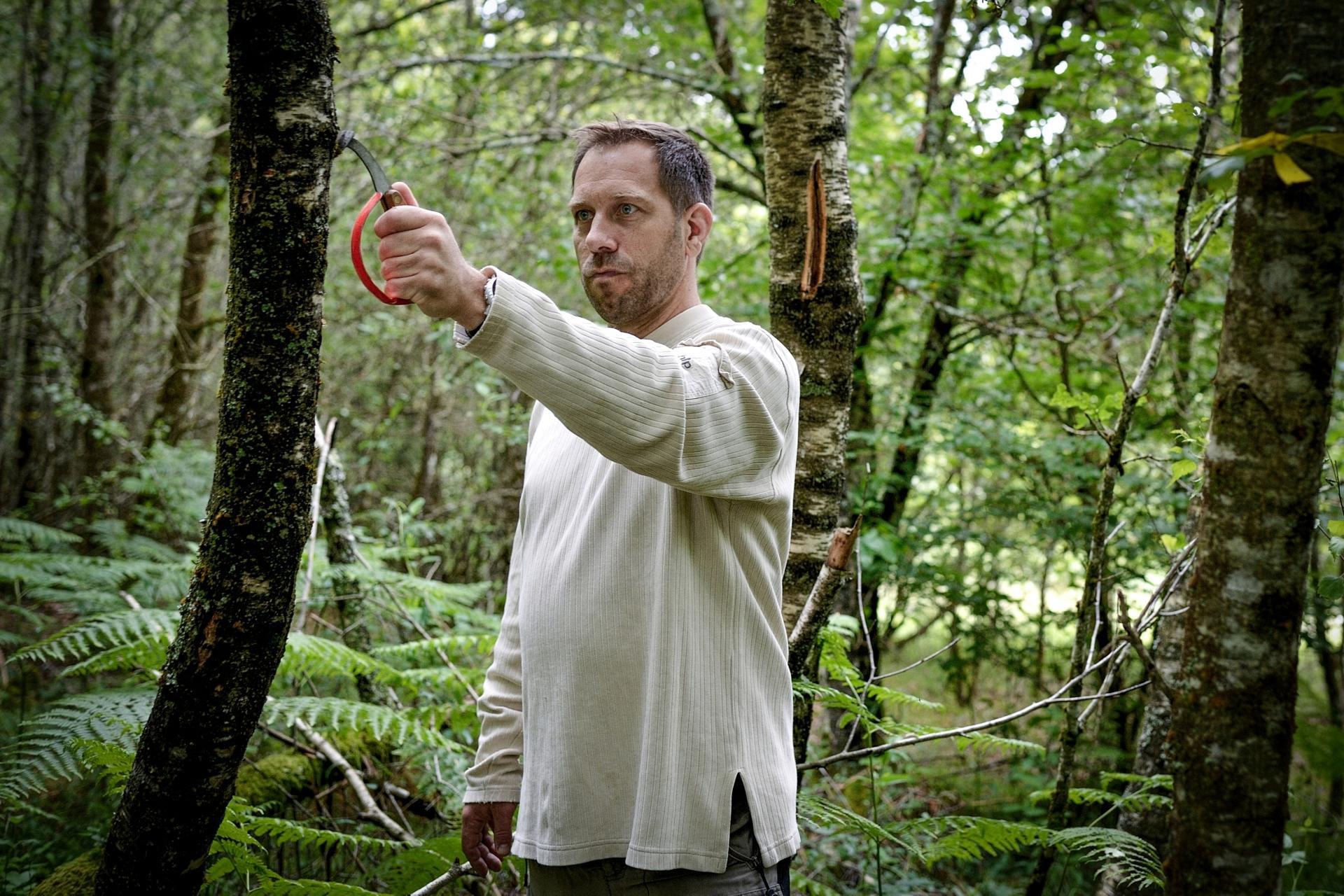 Vincent Magnet utilise une griffe pour marquer les arbres qui pourraient être coupés, afin de provoquer des éclaircies douces, à Saint-Moreil (Creuse), le 30 juin 2021.