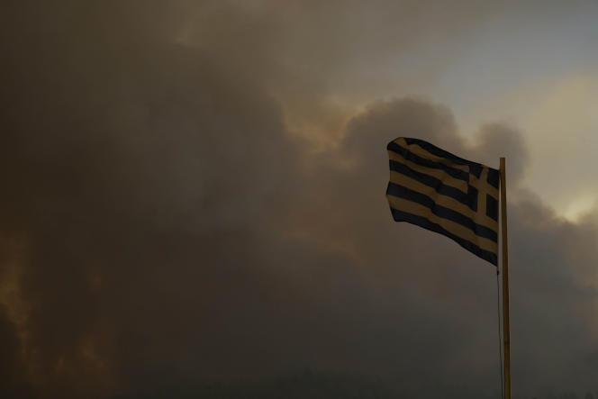 Η ελληνική σημαία καλυμμένη με πυκνό σύννεφο καπνού στις Γούβες, στο νησί της Εύβοιας, στις 8 Αυγούστου 2021.