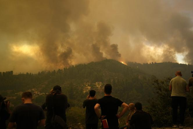 Los vecinos siguen la trayectoria del incendio que se acerca al pueblo de Gouves, en la isla de Evia, el 8 de agosto.