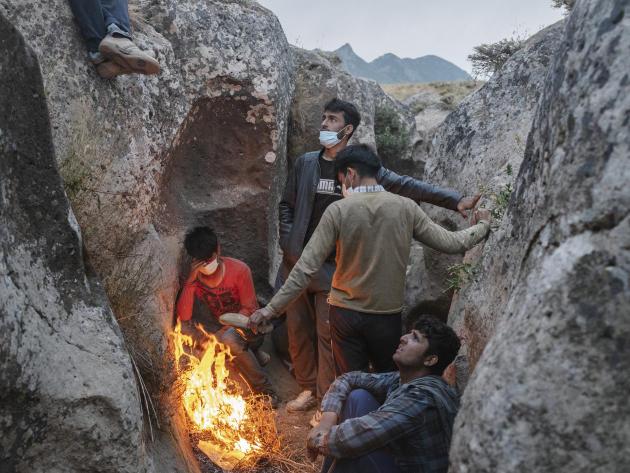 Des migrants se cachent près des rochers après avoir fui pour éviter d'être attrapés par la gendarmerie turque, près de Van, le 6 août 2021.