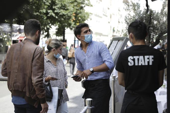 Un serveur contrôle le passe sanitaire de clients d'un restaurant, à Paris, le 9 août 2021.