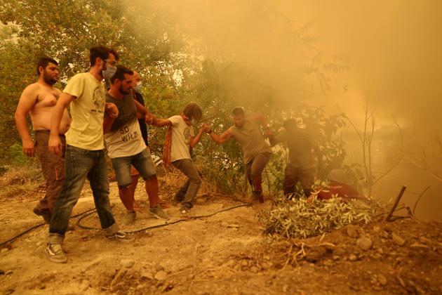 Des habitants de l'île d'Eubée installent des tuyaux d'arrosage pour lutter contre le feu près du village de Gouves, le 8août.