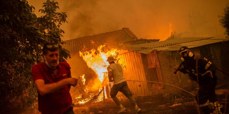 TOPSHOT - A firefighter and locals rush to a burning house in an attempt to extinguish forest fires that are approaching the village of Pefki on Evia (Euboea) island, Greece's second largest island, on August 8, 2021. Hundreds of Greek firefighters fought desperately on August 8 to control wildfires on the island of Evia that have charred vast areas of pine forest, destroyed homes and forced tourists and locals to flee. Greece and Turkey have been battling devastating fires for nearly two weeks as the region suffered its worst heatwave in decades, which experts have linked to climate change. (Photo by ANGELOS TZORTZINIS / AFP)