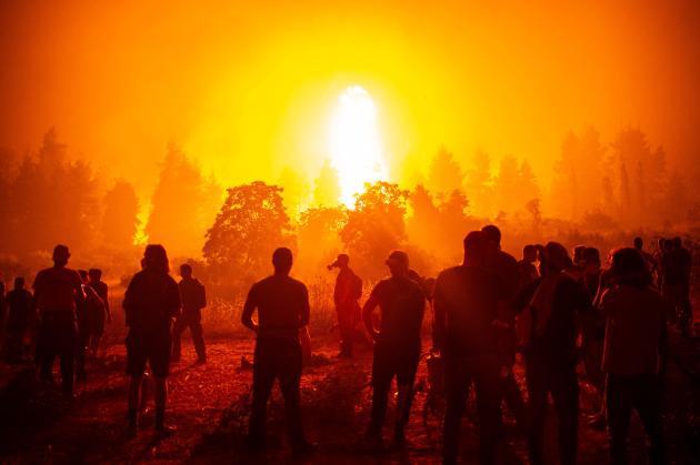 Warga melihat progres kebakaran di Kamatriades, Pulau Evia, pada 9 Agustus 2021.