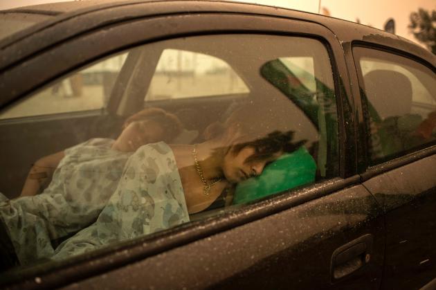 Warga Pefki, di pulau Evia, sedang tidur di mobil mereka setelah mengancam kota mereka pada 8 Agustus 2021.
