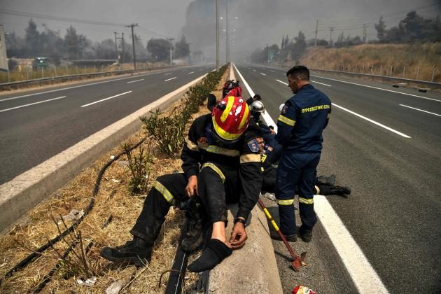 Petugas pemadam kebakaran beristirahat di Afidnes, utara Athena, pada 6 Agustus 2021.