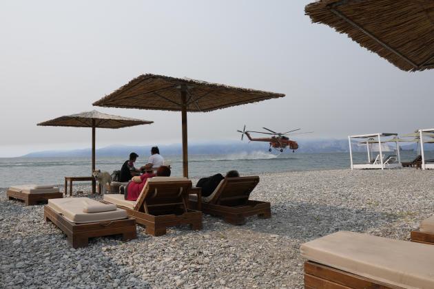 Helikopter pemadam kebakaran mengisi tangki airnya di sepanjang Pantai Pefki di pulau Evia sementara wisatawan menonton pada 9 Agustus 2021.