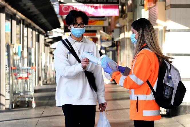 Distribución de máscaras en una calle de Sydney el 11 de agosto.