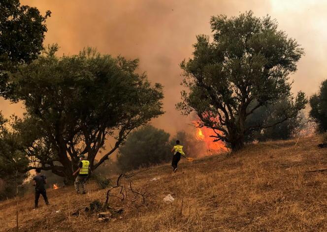 Εθελοντές και πυροσβέστες προσπαθούν να σβήσουν τη φωτιά που καταστρέφει το χωριό Iboudraren, στην περιοχή Tizi Ouzou, Πέμπτη 12 Αυγούστου 2021.