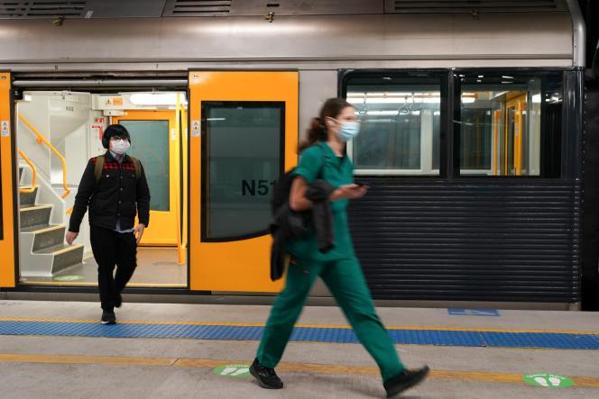 Des passagers portant des masques, à la gare centrale, silencieuse, du centre-ville de Sydney, alors que l'Australie a renforcé ses restrictions pourfreiner la propagation de l'épidémie de Covid-19, le 12 août 2021.