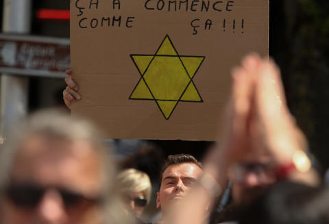 A demonstrator holds up a placards with a 'Yellow Star' - 'it starts like this' during a national day of protest against the compulsory Covid-19 vaccination for certain workers and the compulsory use of the health pass called for by the French government in Reims on July 31, 2021. (Photo by François NASCIMBENI / AFP)