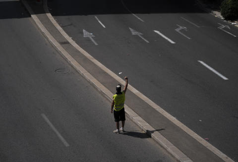 A protester raises his fist in front of French riot police in Marseille, southern France, Saturday, Aug. 14, 2021. Thousands of people, from families to far-right sympathizers, marched in dozens of cities across France for a fifth straight Saturday to denounce a COVID-19 health pass needed to access restaurant, long-distance trains and other venues. (AP Photo/Daniel Cole)