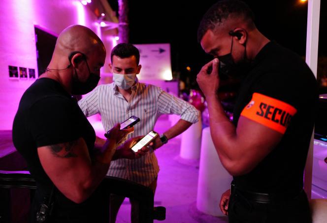 Des agents de sécurité vérifient le passe sanitaire d'un client dans la discothèque La Dune,à La Grande Motte, le 9 juillet 2021.