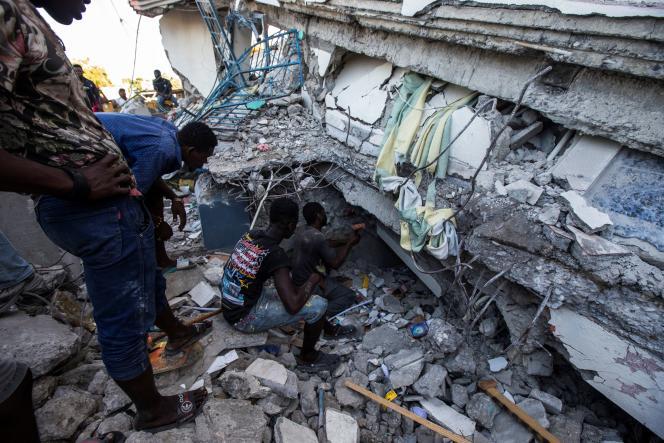 Des habitants cherchent d'éventuelssurvivants dans les décombres d'une maison, samedi 14 août aux Cayes, en Haïti.
