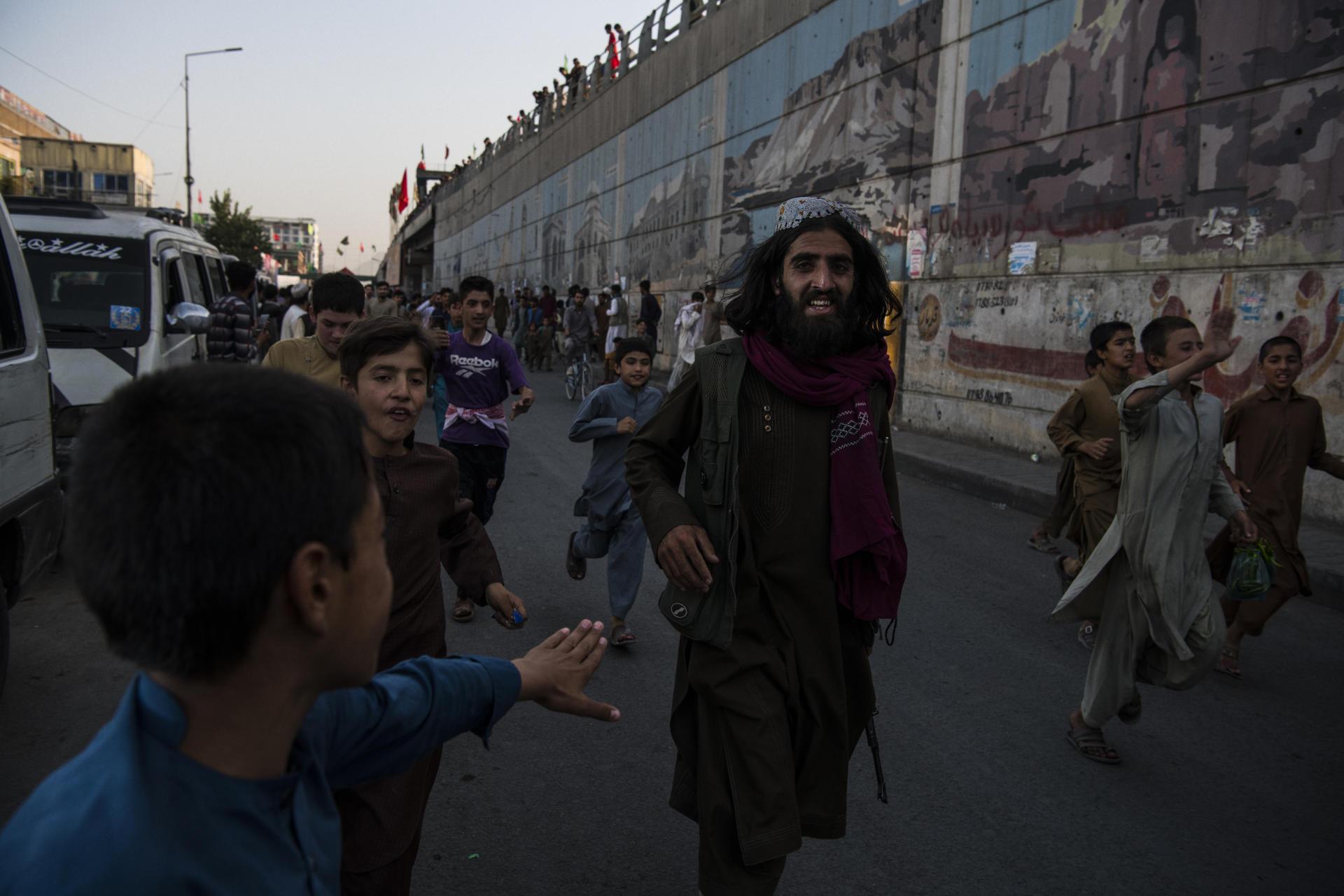 Un combattant taliban, escorté par la foule dans une rue de Kaboul, le 15août2021.