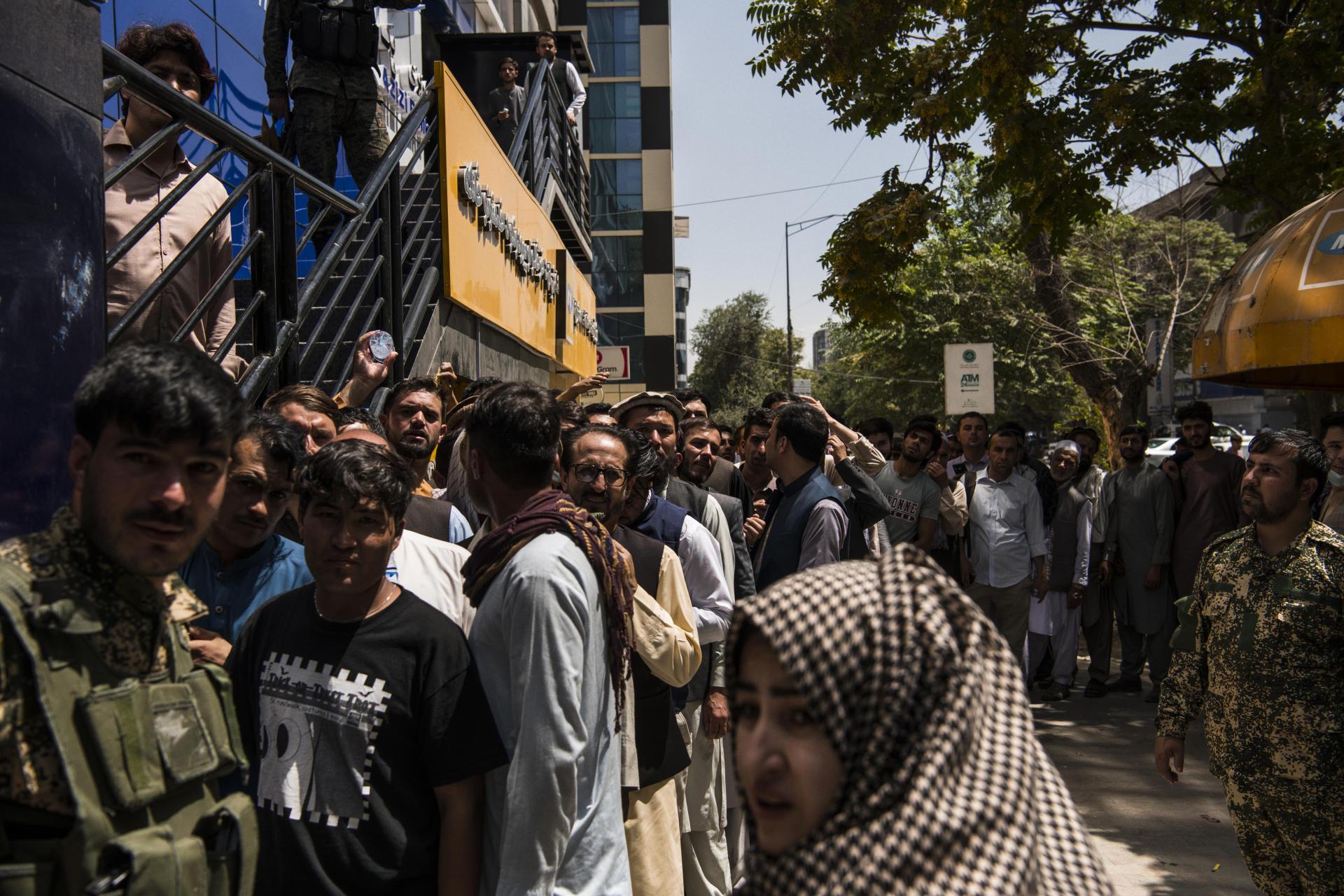 Des Afghans patientent devant une banque à Kaboul, le 15août2021.