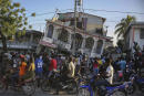 People gather outside the Petit Pas Hotel, destroyed by the earthquake in Les Cayes, Haiti, Saturday, Aug. 14, 2021. A 7.2 magnitude earthquake struck Haiti on Saturday, with the epicenter about 125 kilometers (78 miles) west of the capital of Port-au-Prince, the US Geological Survey said. (AP Photo/Joseph Odelyn)