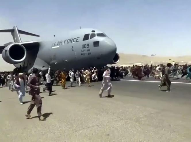 Des centaines de personnes tentent d'escalader un avion de l'US Air Force quittant Kaboul, le 16 août 2021.