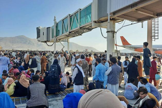 Des Afghans sur le tarmac de l'aéroport de Kaboul, le 16août2021.