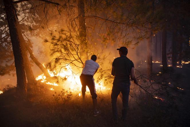 Warga mencoba memadamkan api di dekat Chefchaouen, Maroko, pada 15 Agustus 2021.