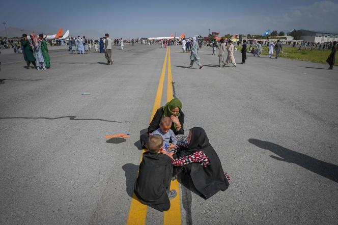 Des Afghans attendent sur le tarmac de l'aéroport de Kaboul, le 16 août 2021.